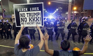 Protesters outside the Trump rally in Phoenix raise their hands after police used teargas to disperse the crowd.