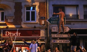 A man, believed to be an England fan, climbs on a signpost outside a bar in Lille.