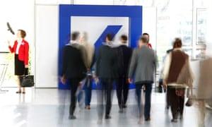 People walk past a Deutsche Bank logo