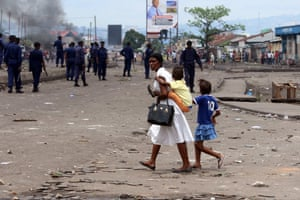A woman and her children pass by the riot police in Kinshasa