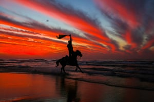 Gaza: A Palestinian rides on the beach at sunset