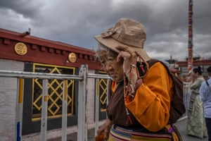 A Tibetan Buddhist woman walks the kora in front of the Jokhang Temple, a UNESCO heritage site