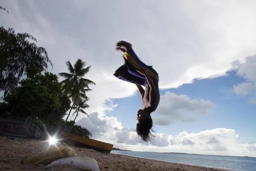 Children from the village of Nanikai on South Tarawa performing acrobatics on the beach.