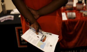 A job seeker holds literature while waiting to speak with a hiring manager at a career fair in San Francisco in July.