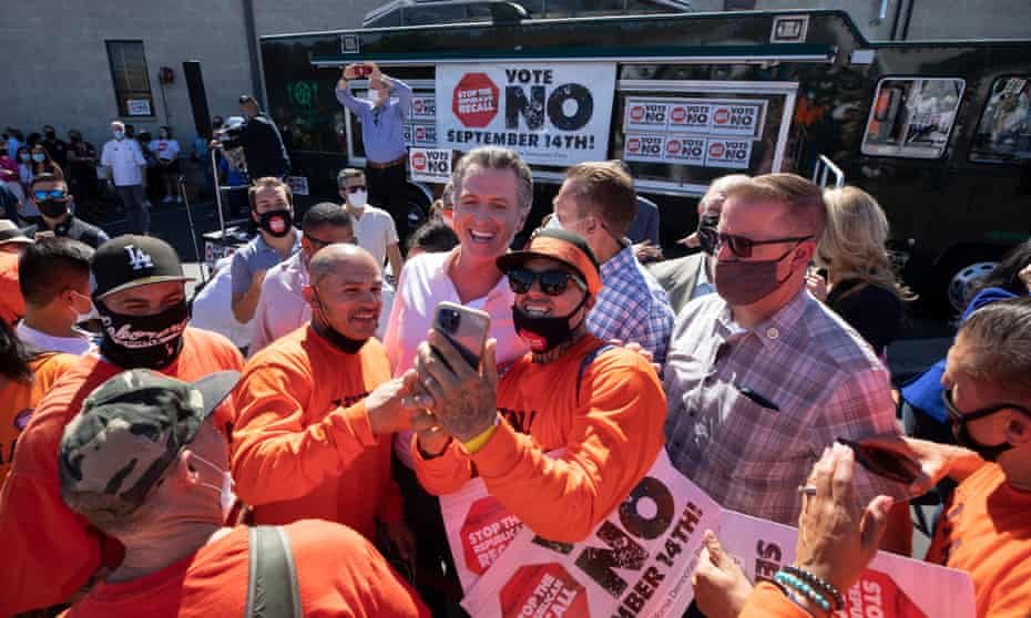 Newsom takes a picture with Joseph Martinez, left, and Christopher Gray following a rally on Sunday in Sun Valley.