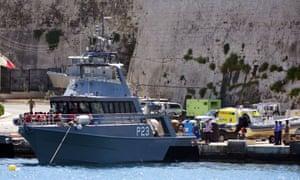 People prepare to disembark from a Maltese patrol boat