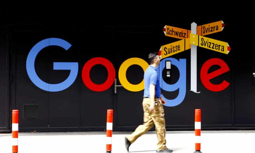 A man walks past a Google sign
