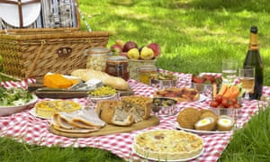Picnic Laid Out On Cloth on the grass with food, hamper, sparkling wine, glasses.