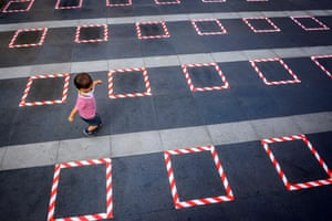 A child wearing a protective facemask runs on a sidewalk marked for social distancing in front of a Buddhist shrine in Bangkok