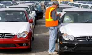 A worker at the Port of Long Beach checks a shipment of Mercedes.