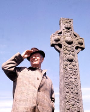 Sir Kenneth Clark standing by the Celtic Cross on the remote island of Iona.