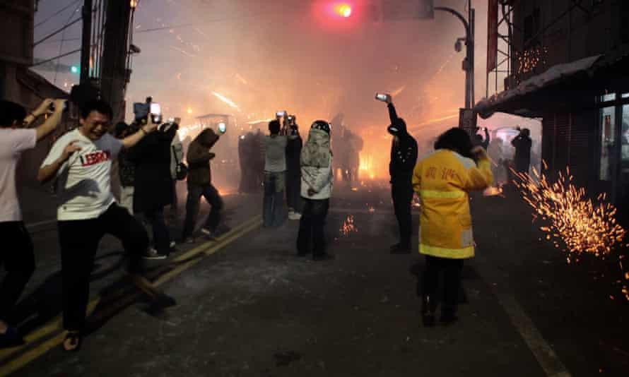 People on the streets as firecrackers soar overhead
