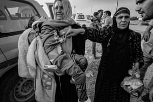 Distraught families with children injured in a landmine blast as they fled the front line are seen in Gogjali, east of Mosul, in 2016