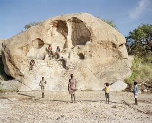 Young Hadza boys climb a large stone rock next to their camp