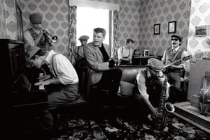English pop group Madness pose during the filming of the promotional video to their single 'Our House' in London in 1982. Left to right: Mike Barson on piano, Chas Smash on trumpet, bassist Mark Bedford, vocalist Suggs, drummer Daniel Woodgate, sax player Lee Thompson and guitarist Chris Foreman