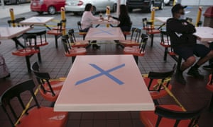 Tables are marked with X's for social distancing in the outdoor dining area of a restaurant in Los Angeles on Wednesday.