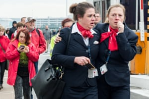 Airport staff react as they walk away from Brussels airport after explosions rocked the facility