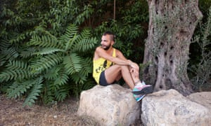Lawrence, LGBT refugee, sitting on a rock next to a tree