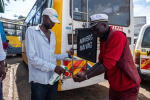 A matatu conductor in the familiar burgundy-red uniform disinfects his hands between shifts