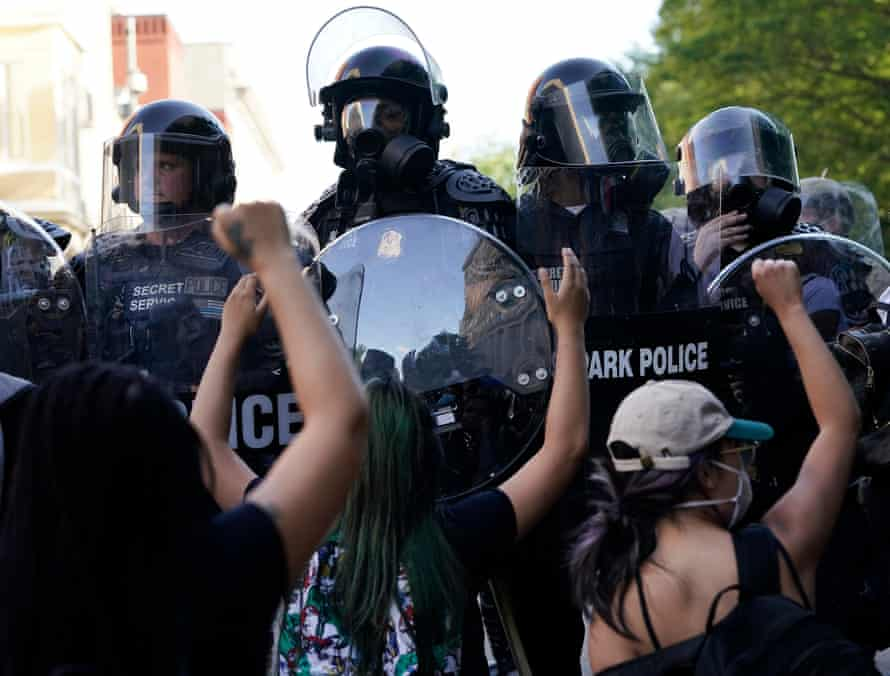 Protesters demonstrating against the death of George Floyd kneel in front of police carrying Scorpion shields in Washington DC on 1 June.