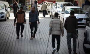 Men with crutches walk down the street in Gaza.
