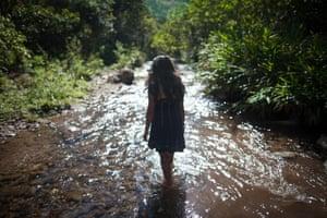 Yanina Avila, 18, the daugher of José de los Santos Sevilla, walks along a river