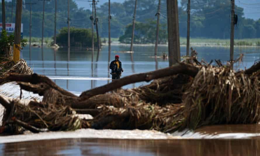 Um homem atravessa o lixo e as enchentes causadas pelo furacão Eta em Honduras.
