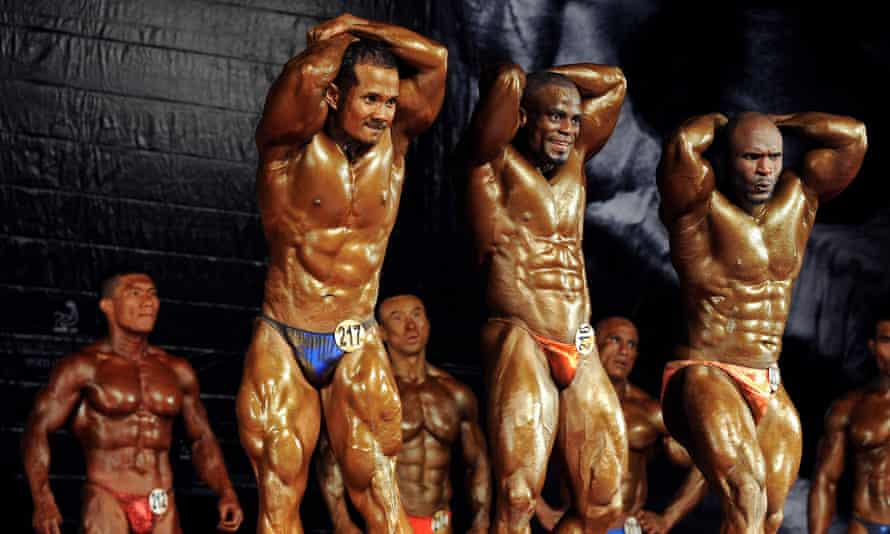 Contestants flex their muscles on stage during the first round of the men's bodybuilding 85-kg category at the Asian and World Bodybuilding and Physique Sport Championships in Bangkok on October 7, 2011. AFP PHOTO / Pornchai KITTIWONGSAKUL (Photo credit should read PORNCHAI KITTIWONGSAKUL/AFP/Getty Images)