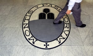 A man walks past the logo for the Monte Dei Paschi Di Siena bank