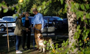 Massachusetts Senator Elizabeth Warren, her husband Bruce and their dog, Bailey, wait to take the stage at a campaign stop in Hollis, New Hampshire, on September 27