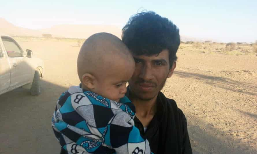 Ezzaldeen Tuaiman holding his son.