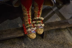 A participant wears a traditional outfit, which includes intricately decorated shoes