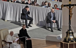 The Swedish environmental activist Greta Thunberg, centre top, crouches behind attendees to get to her seat as Pope Francis delivers his weekly message