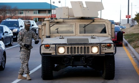 A member of the national guard walks by a Humvee in Clayton, Missouri in November 2014 following a night of rioting in nearby Ferguson.