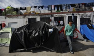 A man emerges from a tent advertising phone recharges at the former concert venue Barretal in Tijuana.