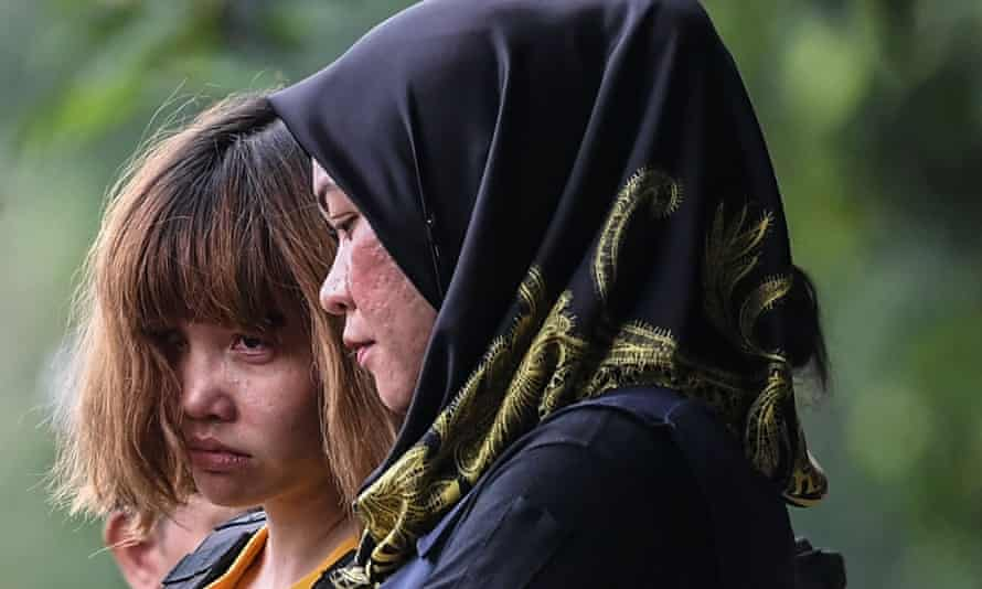 Doan Thi Huong (left) is escorted to court in Sepang by a policewoman.