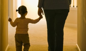 Child and adult walking together, holding hands