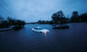An abandoned car's hazard lights continue to flash as it sits submerged in a rising flood waters during pre-dawn hours after Hurricane Florence struck in Wilmington, North Carolina,on Saturday.