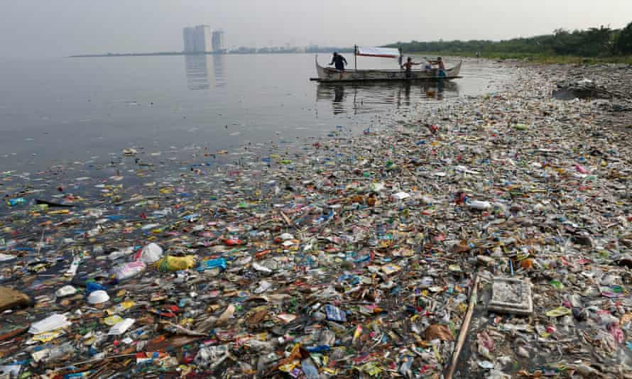 Fishermen float onboard a boat amid mostly plastic rubbish in Manila Bay, the Philippines. Humans have introduced 300m metric tonnes of plastic to the environment every year.