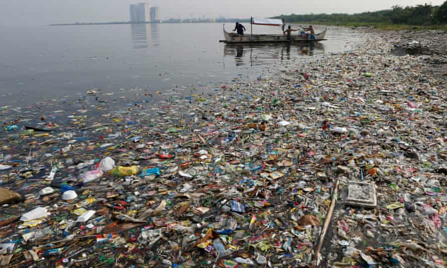 fishing boat works amid garbage in Manila Bay, the Phillipines