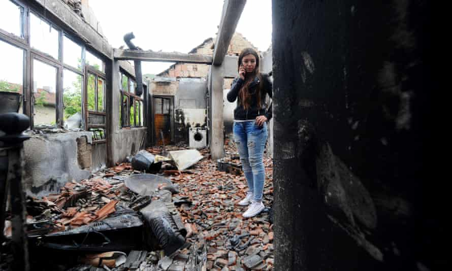 A woman walks in her damaged house after fighting between Macedonian police and an armed group in the town of Kumanovo