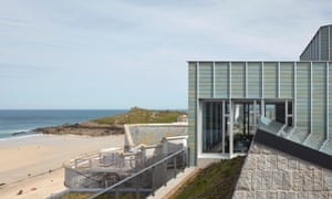 A close-up of the modern Tate St Ives extension with the sandy beach and sea in the distance to the left