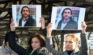 Mourners hold pictures of Naji al-Jarf during his funeral in Gaziantep, southern Turkey.