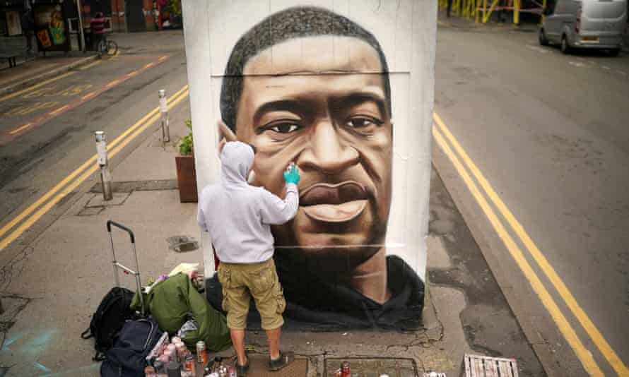 A graffiti artist paints a mural of George Floyd in Manchester last year