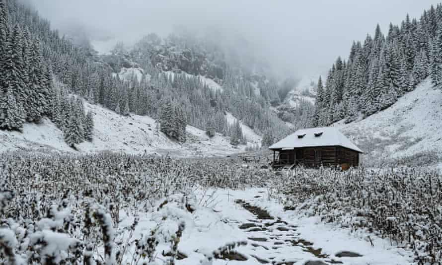 Snow covered fir trees surround a cabin at Valea Rea (The Bad Valley) on Fagaras mountains near Nucsoara, in central Romania.