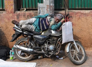 New Delhi, India. An older man sleeps on top of a motorbike in the city's old quarter