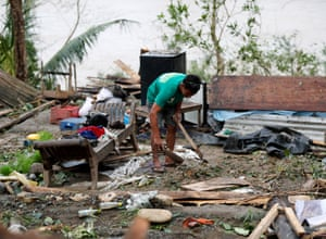A villager collects belongings from what is left of his home in Baggao, the Philippines