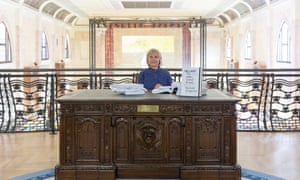 Hillary Clinton poses at an art exhibition, behind a replica of the Oval Office presidential Resolute desk, where she read out her infamously-leaked emails, at an art project in Italy linked to the Venice Biennale last week
