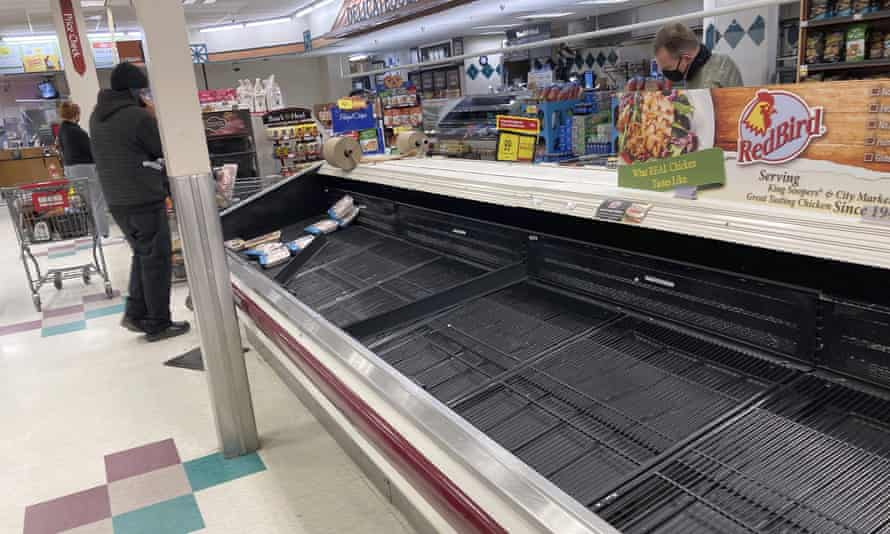 A shopper browses through the few packages of chicken left in a nearly empty refrigerated case in Denver on 11 March.