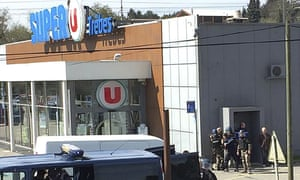 Police outside the supermarket in Trèbes, southern France. An armed man initially took eight people hostage.